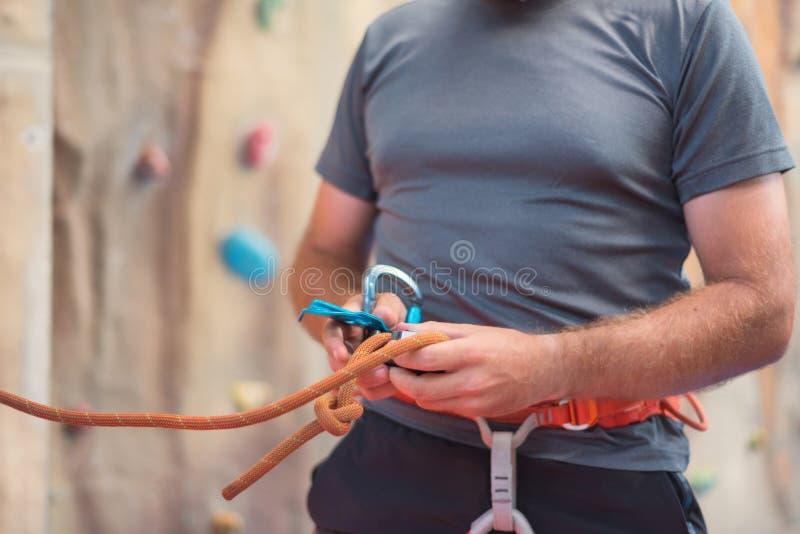 De klimmer die van de rotsmuur veiligheidsuitrusting dragen en materiaal beklimmen binnen, close-upbeeld royalty-vrije stock fotografie