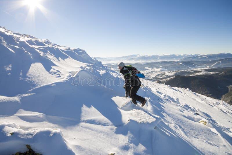 De klimmer die van de toeristenwandelaar in de winterkleding met rugzak gevaarlijke rotsachtige steile die berghelling beklimmen  royalty-vrije stock afbeelding