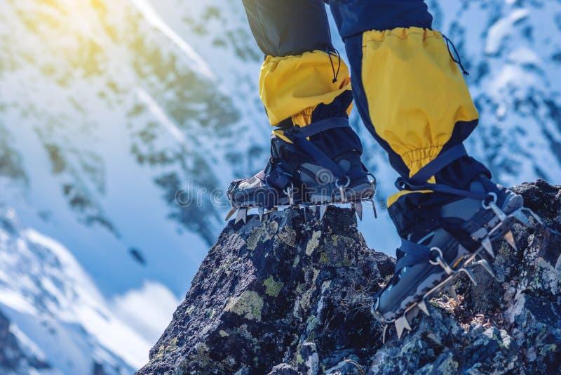 De klimmer in ijskrappen bevindt zich op de rotsen voor de ingang aan de piek op de achtergrond van de sneeuwbergen stock foto's