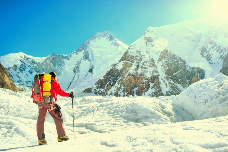 De klimmer met rugzakken bereikt de top van bergpiek succ stock fotografie