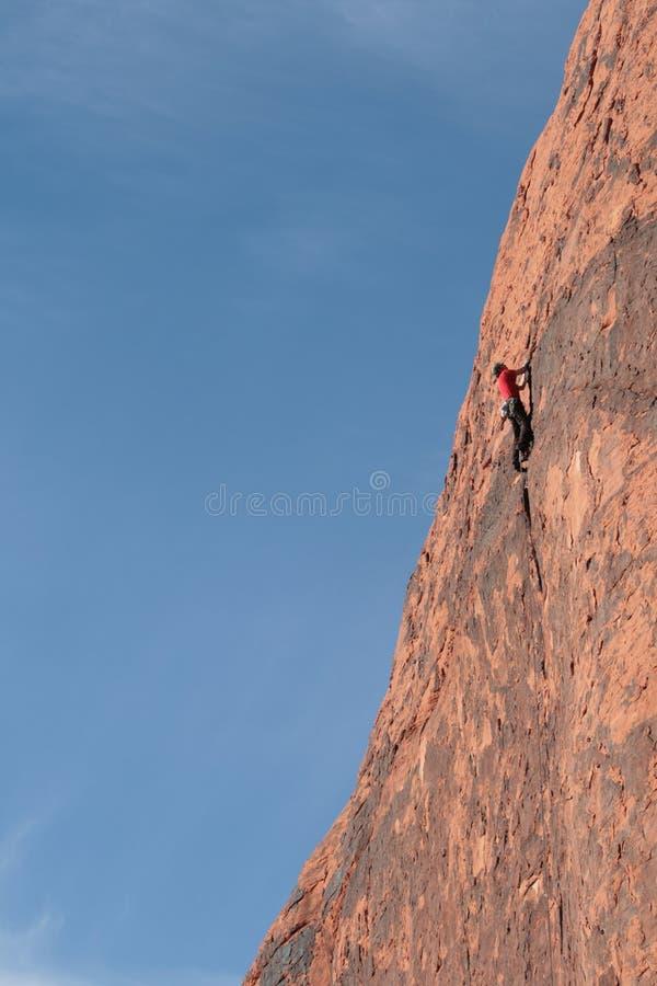 De klimmer van de rots hoog op klip stock foto