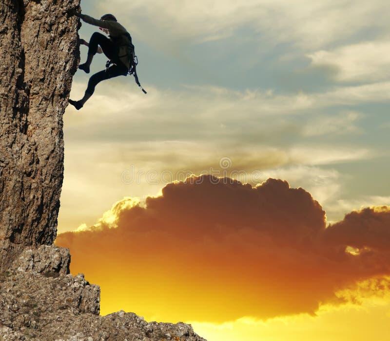 De klimmer van de rots op zonsondergangachtergrond stock afbeelding
