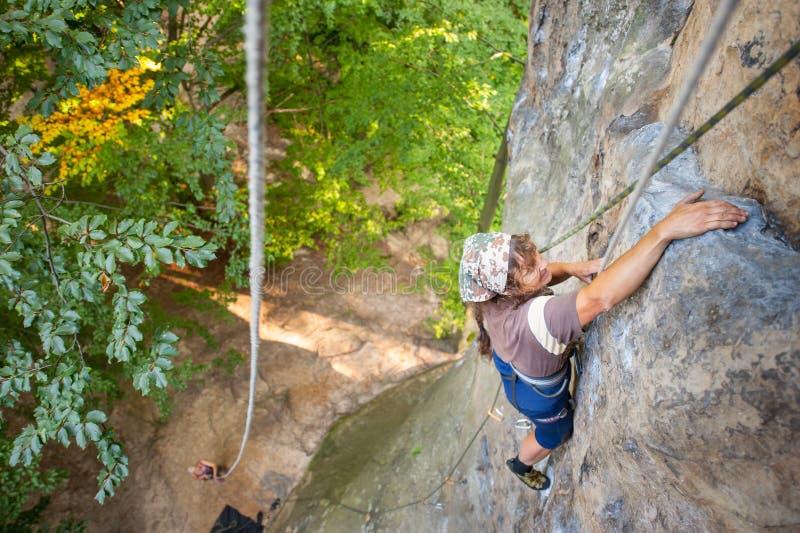 De klimmer van de vrouwenrots beklimt op een rotsachtige muur royalty-vrije stock afbeelding