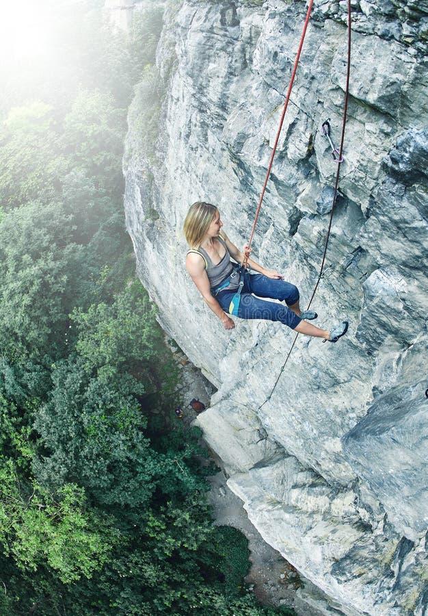 De klimmer van de vrouwenrots op de klip wordt beklommen die stock foto