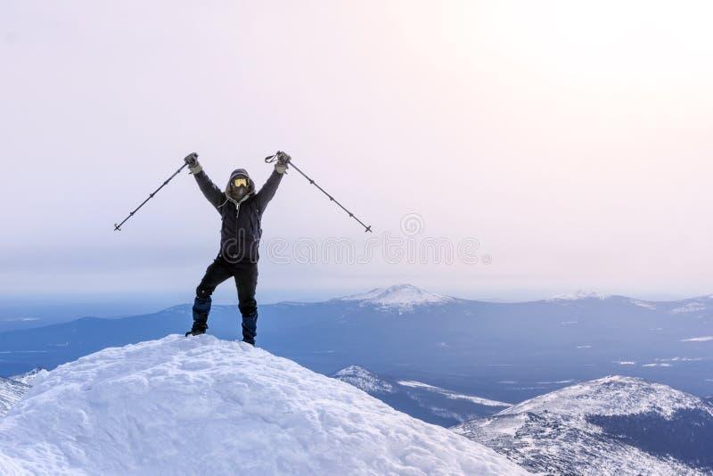 De klimmer verheugt zich, bereikend de bovenkant van de berg stock foto
