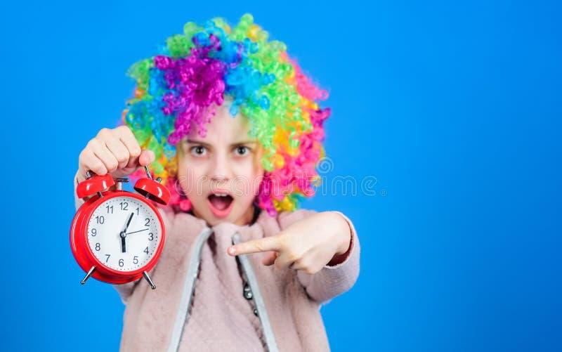De klok die weg de tijd tikken Aanbiddelijk klein kind die met kleurrijk pruikenhaar op wekker voor de nauwkeurige tijd richten royalty-vrije stock afbeeldingen