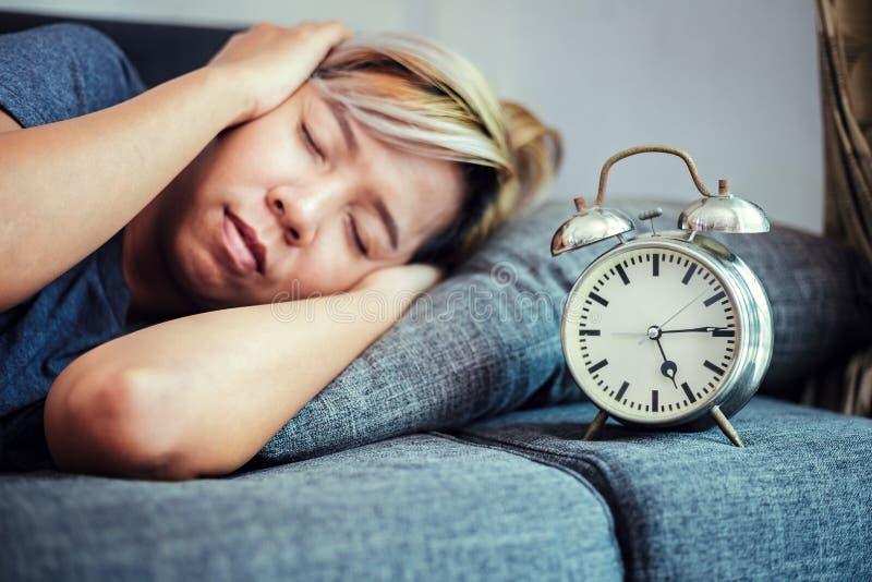 De klok is op het bed dichtbij vrouwen het slapen stock foto