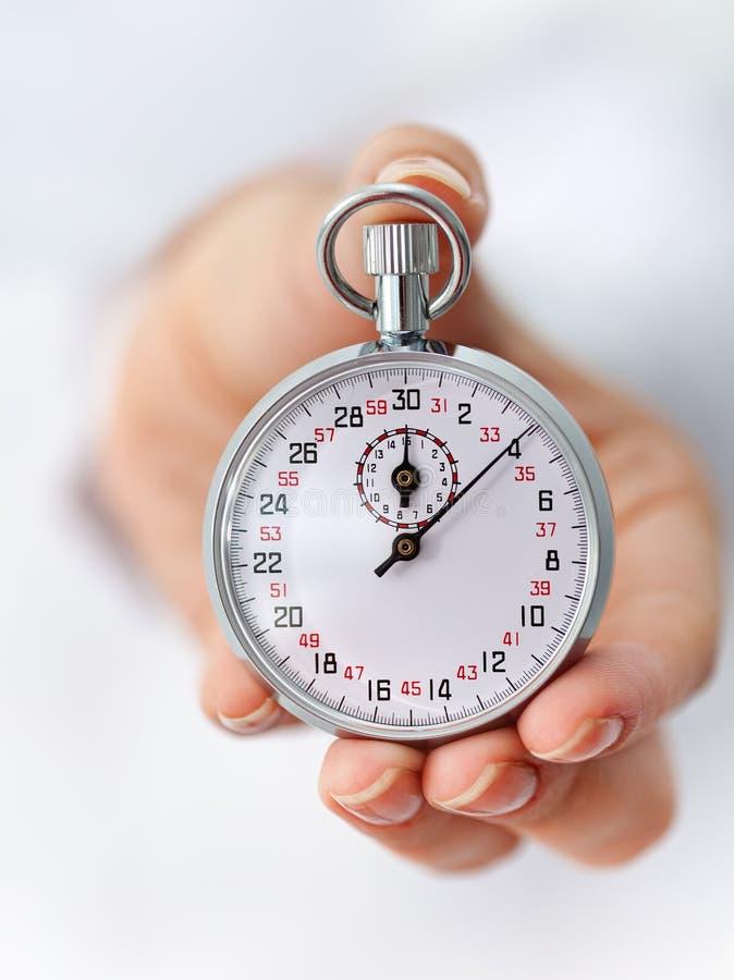 De klok tikt - chronometer in vrouwenhand stock afbeelding