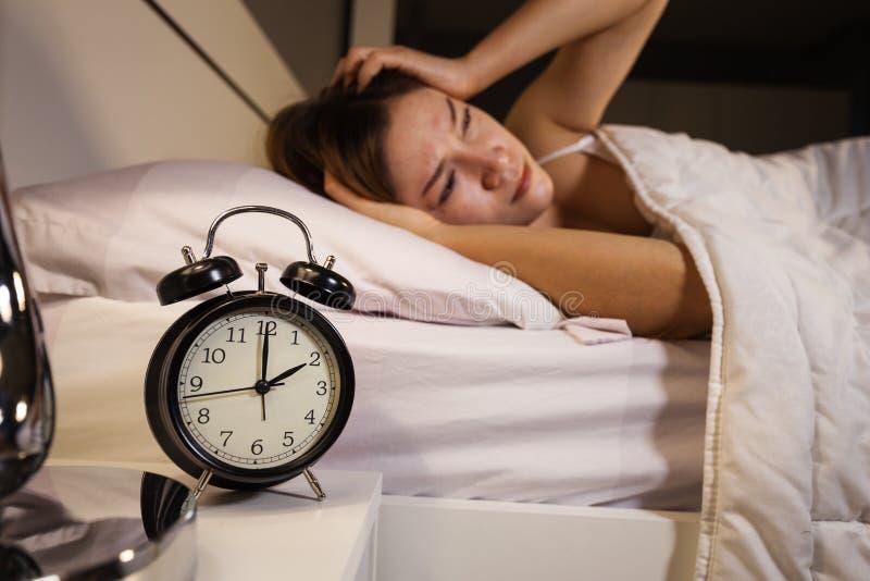 De klok toont de klok en de vrouw van 2 O ` slapeloos op bed royalty-vrije stock afbeelding