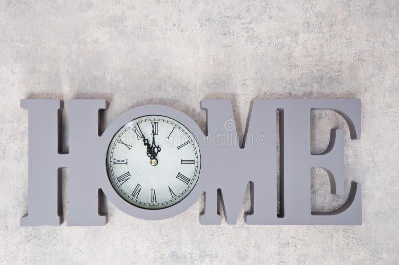 De klok toont tijd thuis, lag de vlakte Tijd, het nieuwe leven en generatie, hoop en zorg Symbool van de huis het woongelijkheid  royalty-vrije stock afbeelding