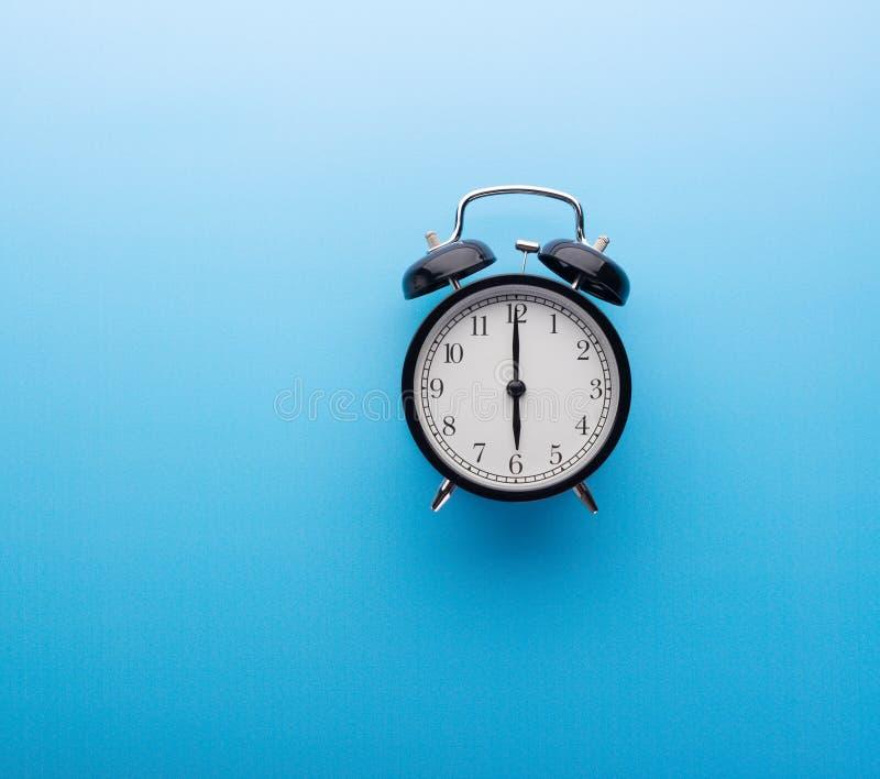 De klok van het alarm op blauwe achtergrond hoogste mening Zes uur stock afbeelding