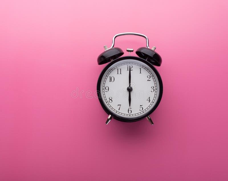 De klok van het alarm op roze achtergrond hoogste mening Zes uur royalty-vrije stock fotografie