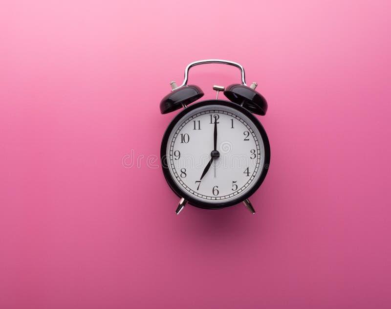 De klok van het alarm op roze achtergrond hoogste mening Zeven uur stock foto