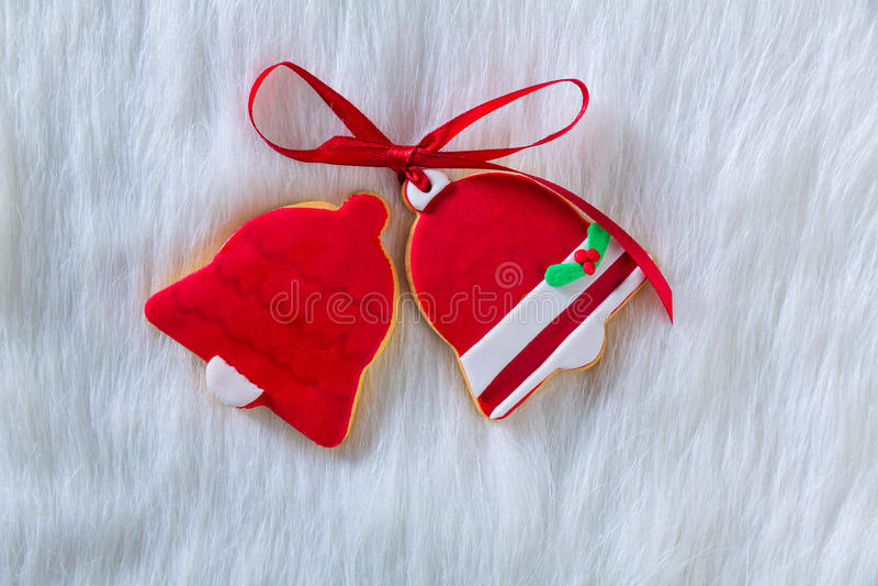 De klokvorm en lint van Kerstmiskoekjes rode op wit bont royalty-vrije stock afbeelding