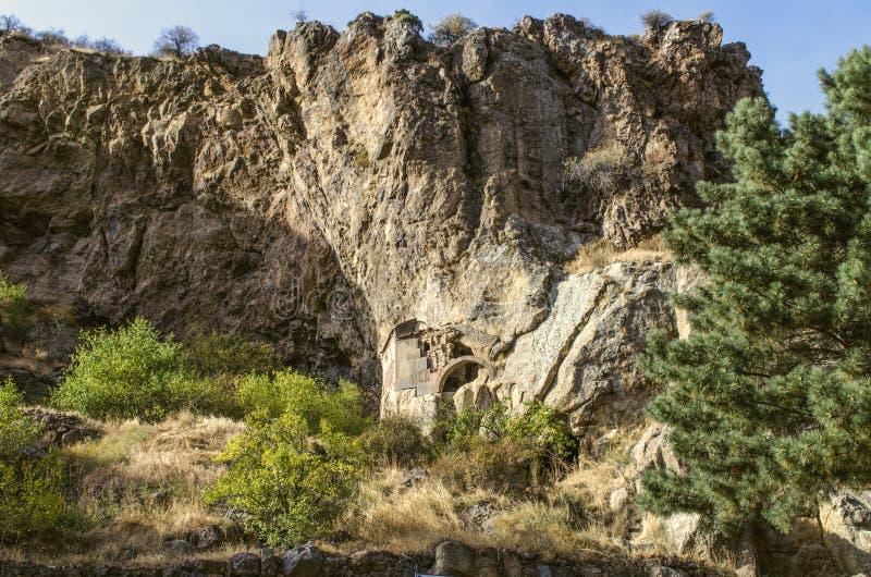 De kloof van Geghama-rand en bewaarde hoek met overspannen ingang aan de holkerk dichtbij Geghard-klooster van Armenië stock foto