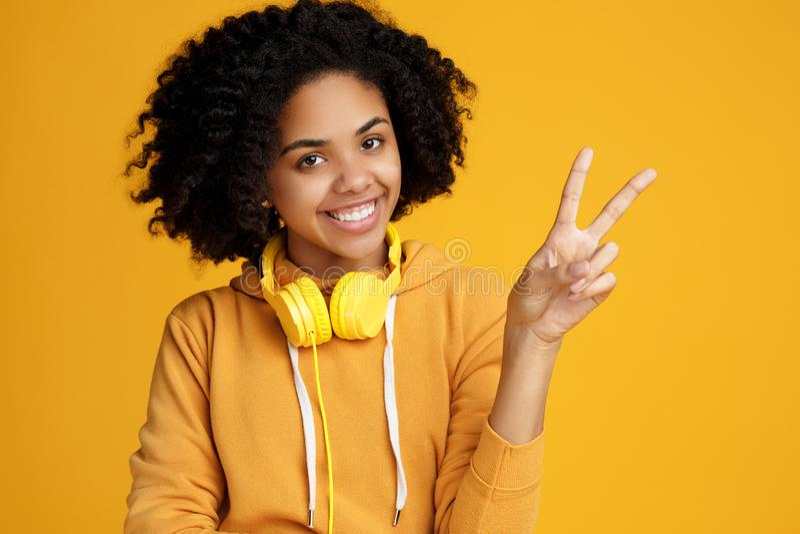 De knappe Afrikaanse Amerikaanse jonge vrouw met heldere glimlach kleedde zich in vrijetijdskleding en hoofdtelefoons die vredesg stock fotografie
