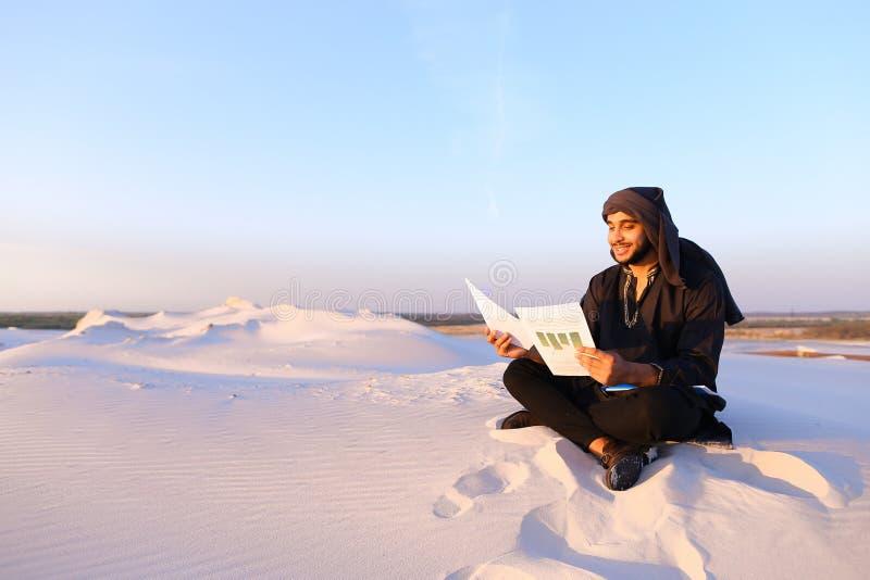 De knappe Arabische mannelijke architect bekijkt documenten en zit op sa royalty-vrije stock fotografie