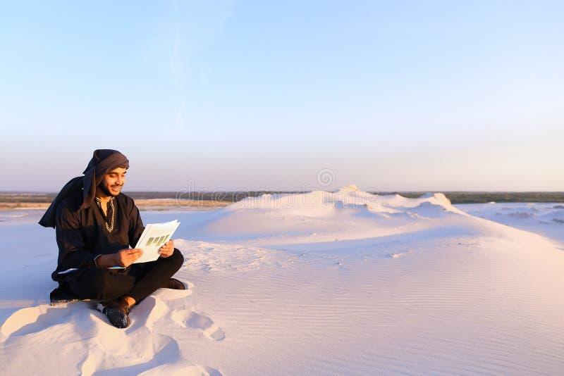 De knappe Arabische mannelijke architect bekijkt documenten en zit op sa royalty-vrije stock foto
