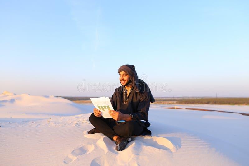 De knappe Arabische mannelijke architect bekijkt documenten en zit op sa royalty-vrije stock afbeeldingen