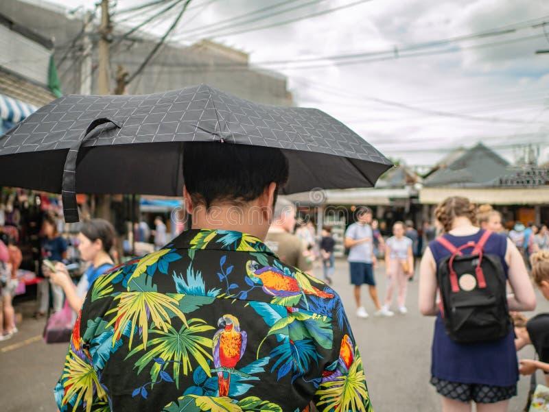 De knappe Aziatische mannelijke paraplu van de de t-shirtholding van slijtagehawai en het lopen in het Chatuchak-park royalty-vrije stock afbeeldingen