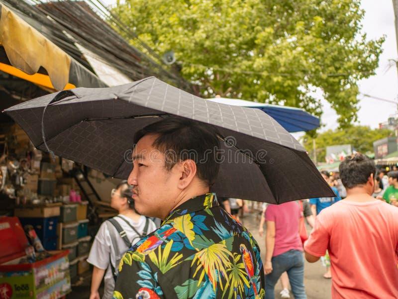 De knappe Aziatische mannelijke paraplu van de de t-shirtholding van slijtagehawai en het lopen in het Chatuchak-park royalty-vrije stock afbeelding