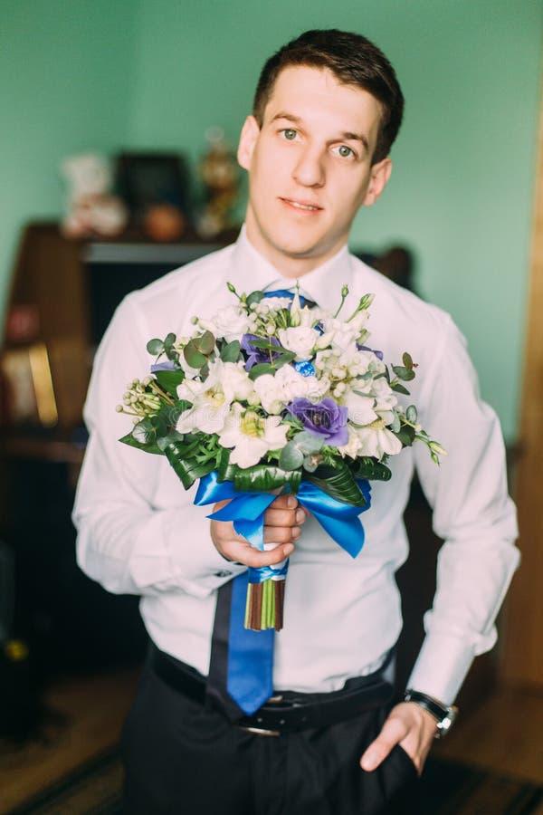 De knappe bloemen van de zakenmanholding en binnen het bekijken camera royalty-vrije stock foto