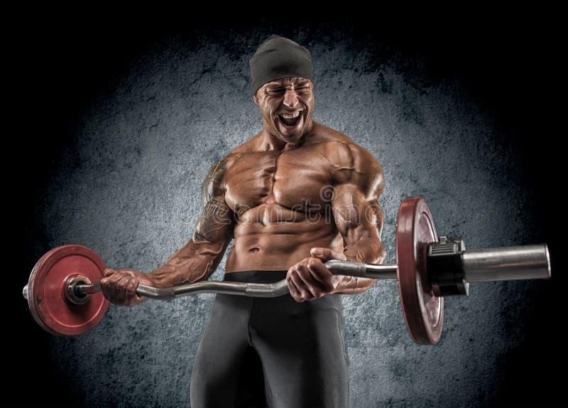 De knappe bodybuilder die van de machts atletische mens oefeningen met bar doen stock foto's