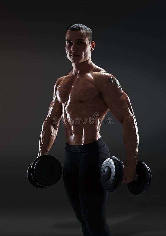 De knappe bodybuilder die van de machts atletische mens oefeningen met dum doen stock fotografie