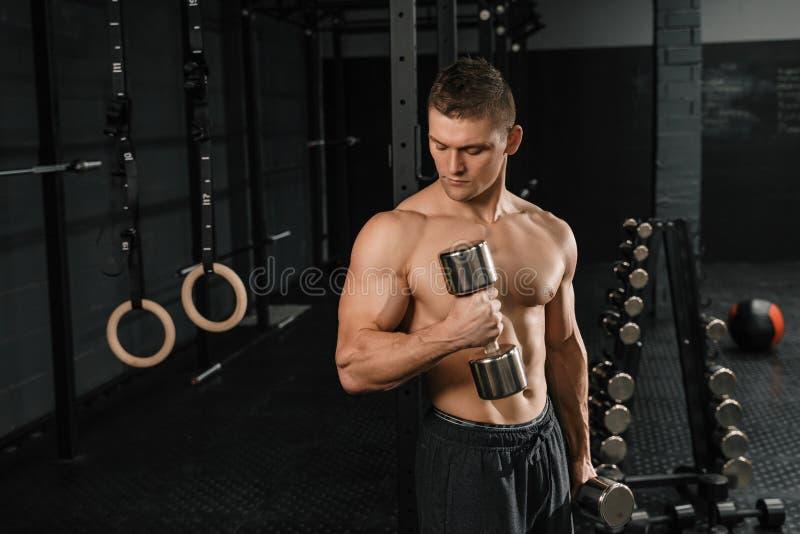 De knappe bodybuilder die van de machts atletische mens oefeningen met domoor doen stock fotografie
