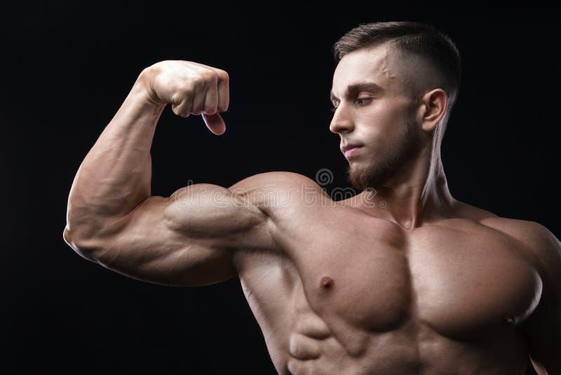 De knappe bodybuilder van de machts atletische mens toont zijn bicepsen aan royalty-vrije stock foto