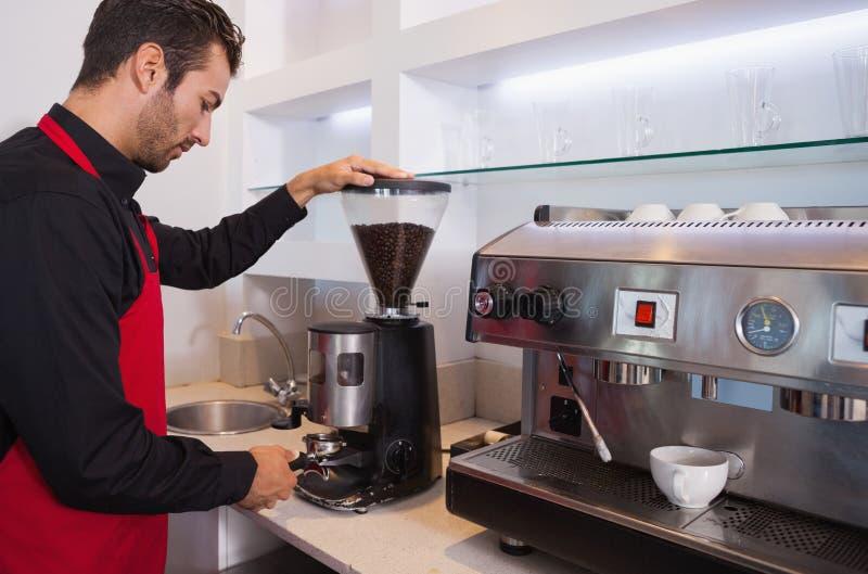 De knappe bonen van de barista malende koffie stock afbeelding