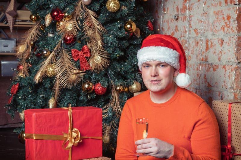 De knappe die kerel in de hoed van de Kerstman houdt een glas van champagnezitting onder de boom door dozen van giften wordt omri stock afbeeldingen