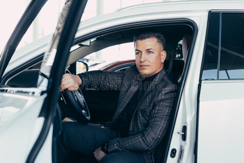 De knappe elegante ernstige mens drijft een witte moderne auto royalty-vrije stock afbeelding