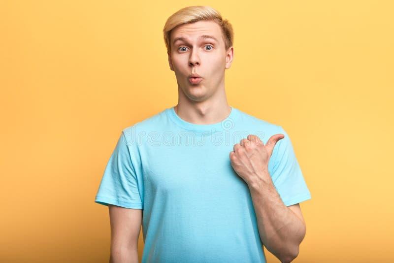 De knappe emotionele mens drukt surprisment uit, toont iets met vinger royalty-vrije stock afbeelding