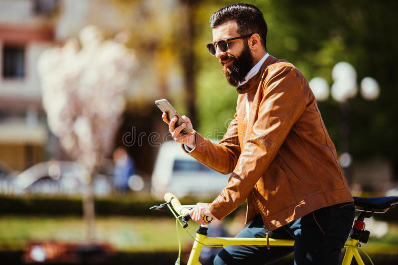 De knappe gebaarde hipstermens gebruikt een slimme telefoon en glimlacht terwijl het berijden van fiets in stad royalty-vrije stock afbeelding