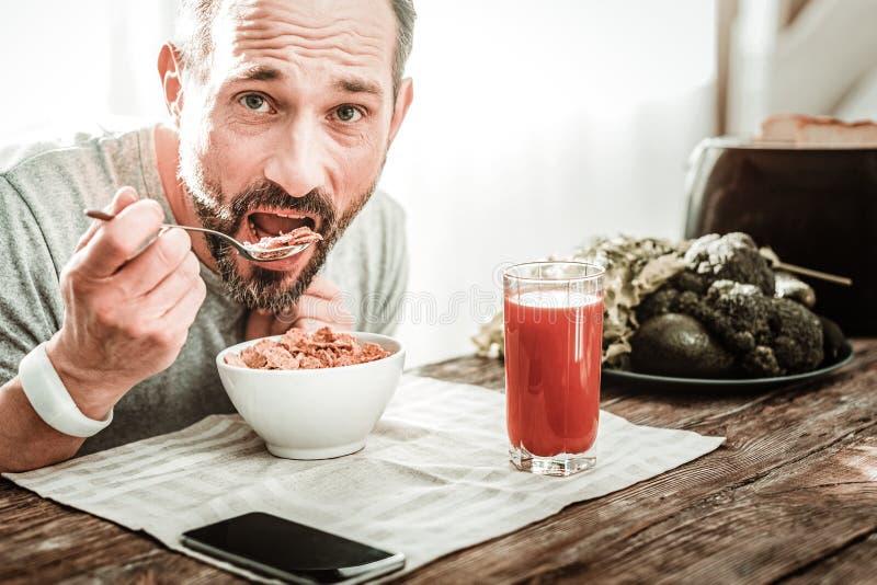 De knappe gebaarde mens die van Nice zijn voedsel eten stock fotografie