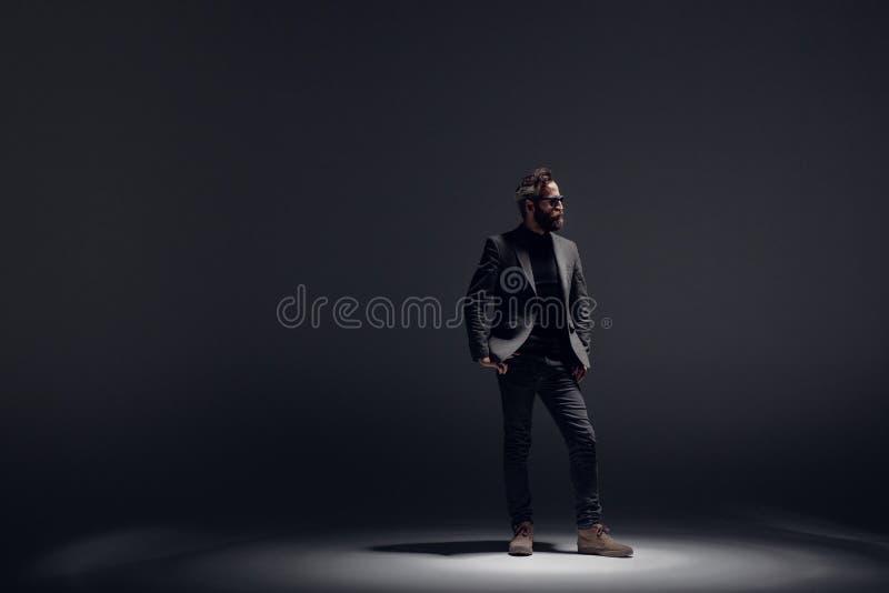 De knappe gebaarde mens die in zwart kostuum dragen, stelt in profiel in studio, op een donkere lighttachtergrond stock afbeelding