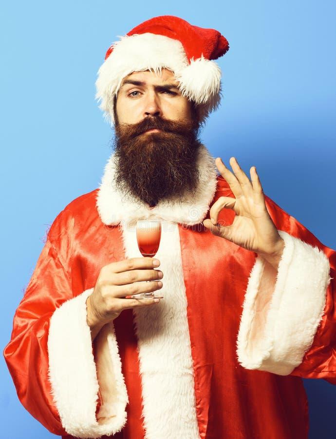 De knappe gebaarde mens van de Kerstman met lange baard op het grappige glas van de gezichtsholding van alcoholisch schot in rode royalty-vrije stock afbeeldingen