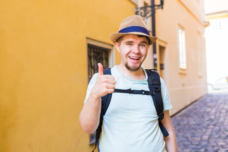 De knappe gebaarde toerist met rugzak maakt reis over stad Mens die en duim opstaan geven stock afbeeldingen