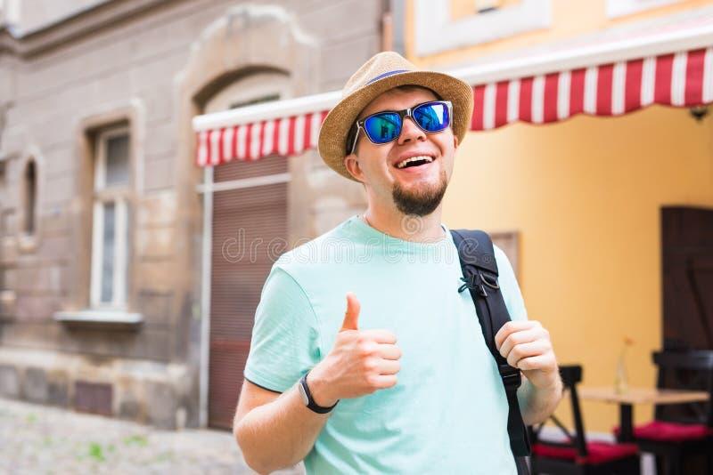 De knappe gebaarde toerist met rugzak maakt reis over stad Mens die en duim opstaan geven stock foto