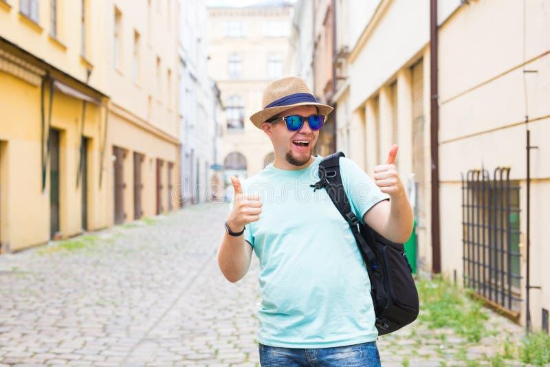 De knappe gebaarde toerist met rugzak maakt reis over stad Mens die en duim opstaan geven stock afbeelding