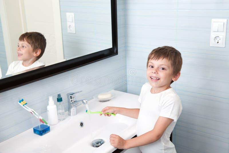 De knappe gezonde tandenborstel van de jongenswas over wasbak royalty-vrije stock afbeelding