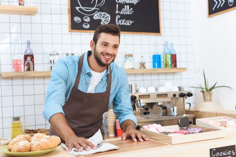 de knappe het glimlachen jonge teller van de barista schoonmakende bar stock fotografie