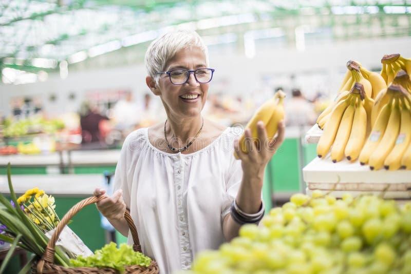 De knappe hogere vrouw koopt bananen bij de markt stock afbeeldingen