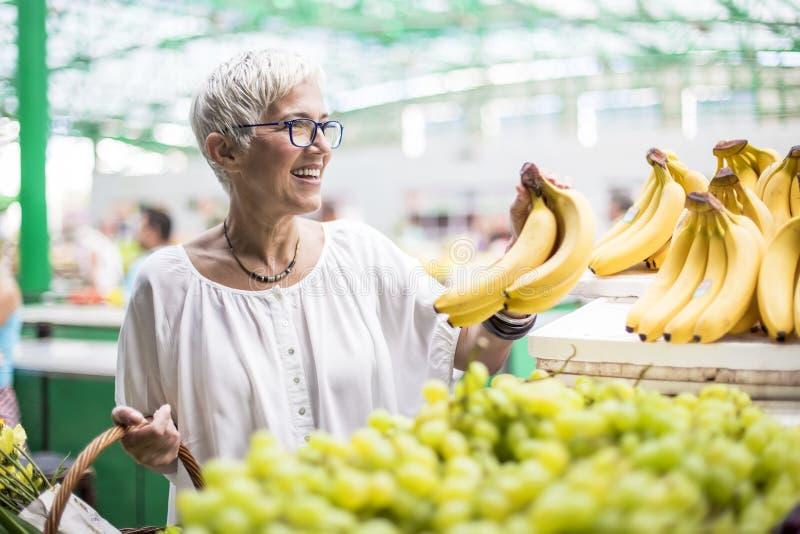 De knappe hogere vrouw koopt bananen bij de markt stock foto's