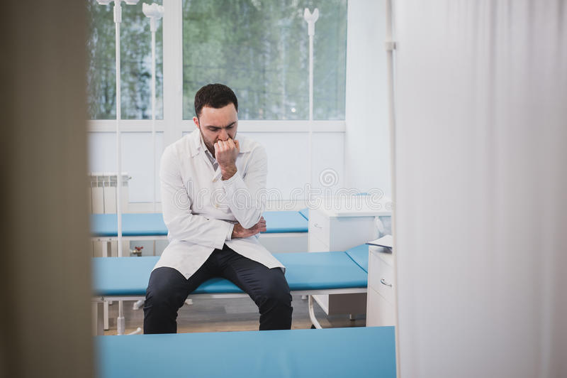 De knappe jonge arts in witte laag zit droevig in het ziekenhuisafdeling stock fotografie