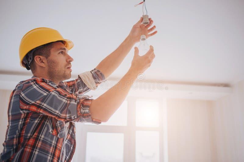De knappe jonge bouwer in een gele bouwhelm verdraait binnen de gloeilamp De man kijkt omhoog royalty-vrije stock afbeeldingen