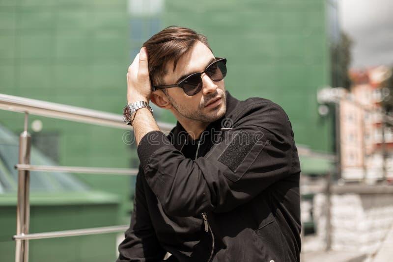 De knappe jonge donkerbruine mens met in kapsel in uitstekende zonnebril in modieus zwart jasje rust in de stad stock afbeelding