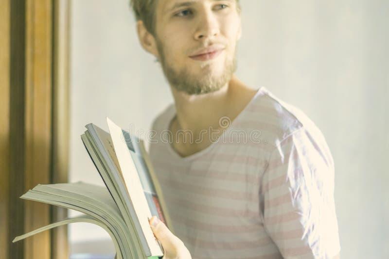 De knappe jonge gebaarde mens draagt kleine stapel van boeken in universitair F royalty-vrije stock foto's