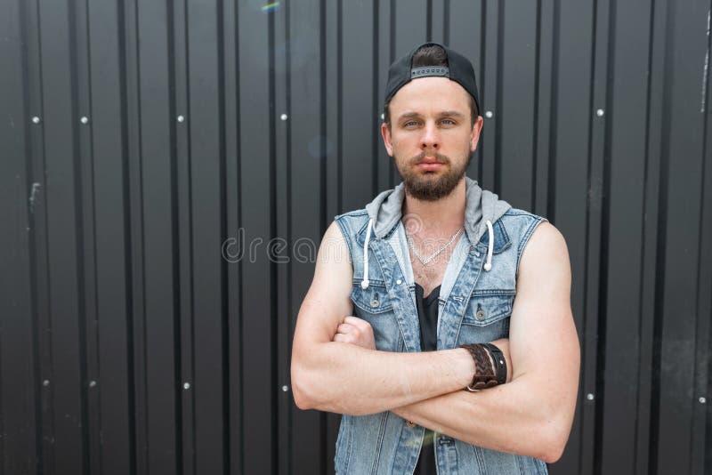 De knappe jonge hipstermens in een modieus blauw denimvest in een t-shirt met een baard in een zwart modieus GLB stelt stock afbeeldingen